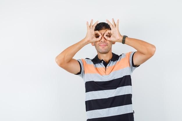 Młody człowiek w t-shirt pokazując gest okularów i wyglądający śmiesznie