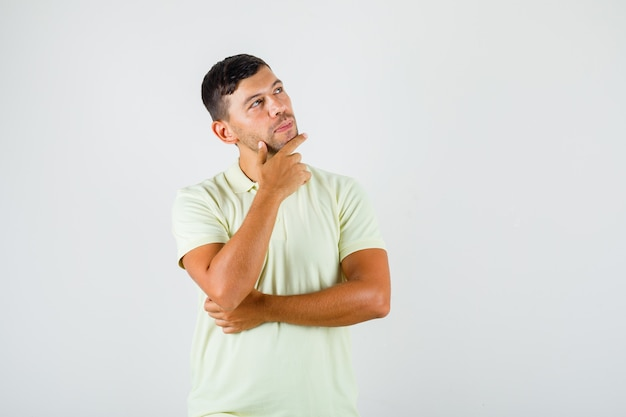Młody człowiek w t-shirt stawiając palec podparcie na brodzie i patrząc zamyślony