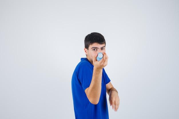 Młody człowiek w t-shirt, trzymając plastikową butelkę i patrząc pewnie, widok z przodu.