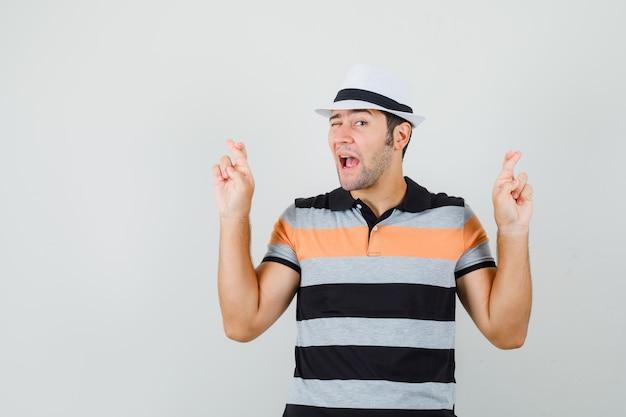 Młody człowiek w t-shirt w paski, kapelusz stojący ze skrzyżowanymi palcami i szuka szalonego miejsca na tekst
