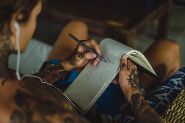 Młody człowiek w tatuażach w słuchawkach słucha muzyki i rysuje w zeszycie.