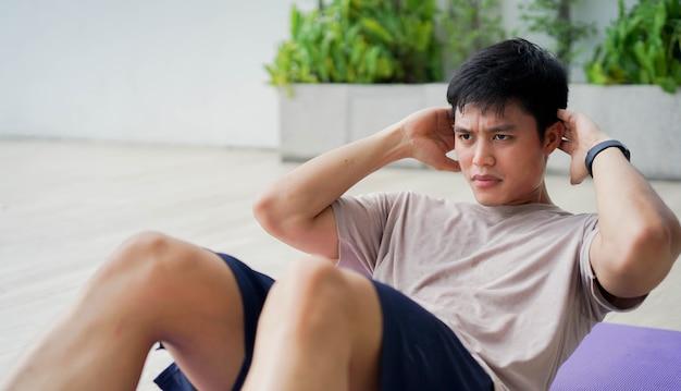 Młody człowiek w treningu wzór sit-up na macie do ćwiczeń w domowej siłowni, rano