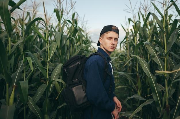 Młody człowiek w ubranie i plecak stojący na polu z kukurydzą