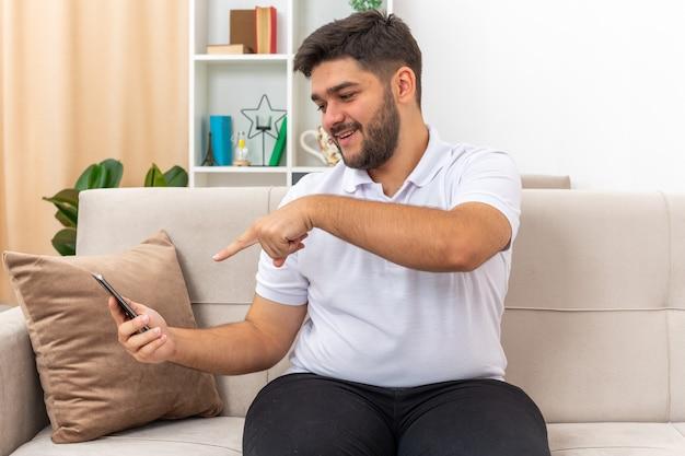 Młody człowiek w ubranie, trzymając smartfon, wskazując palcem wskazującym na to szczęśliwy i pozytywny siedzi na kanapie w jasnym salonie