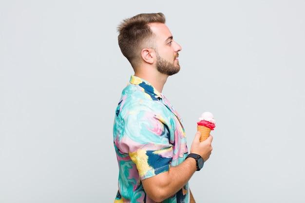 Młody człowiek w widoku profilu chce skopiować przestrzeń do przodu, myśląc, wyobrażając sobie lub marząc