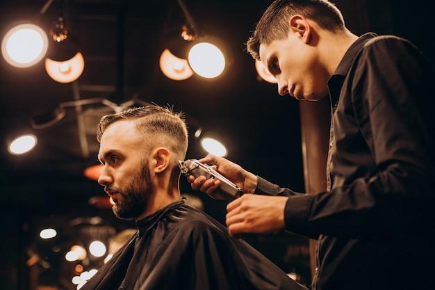 Młody człowiek w zakładzie fryzjerskim przycinanie włosów
