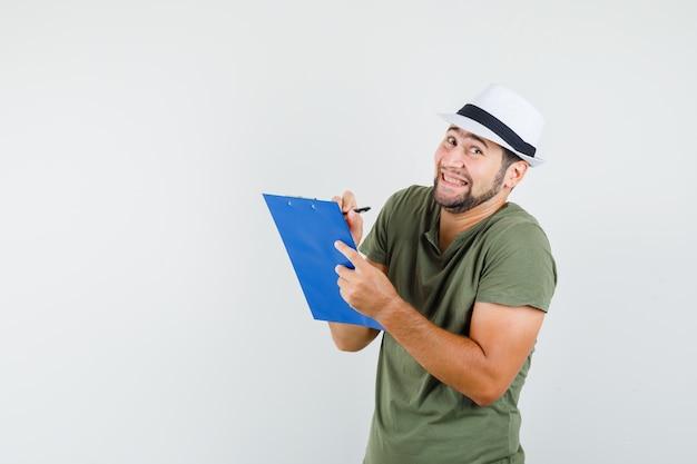 Młody człowiek w zielonej koszulce i kapeluszu, robienie notatek w schowku i wesoły wyglądający