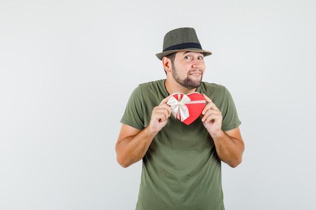 Młody człowiek w zielonej koszulce i kapeluszu, trzymając pudełko i patrząc ukochanej