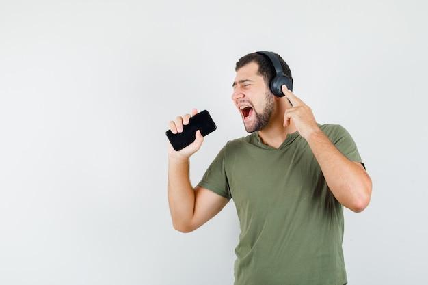 Młody człowiek w zielonej koszulce śpiewa do telefonu komórkowego jak mikrofon i szuka komiksu