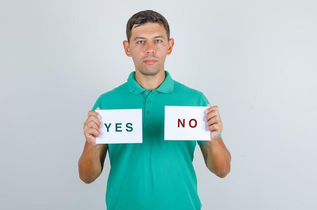 Młody człowiek w zielonej koszulce, trzymając arkusze papieru z odpowiedziami i patrząc poważny, przedni widok.