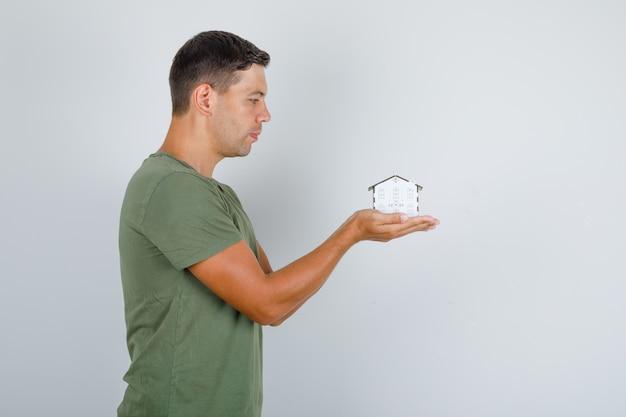 Młody człowiek w zielonej koszuli armii, trzymając model domu i patrząc z nadzieją.
