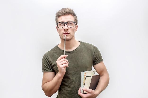 Młody człowiek w zielonej koszuli trzymać książki i ołówek w ręce