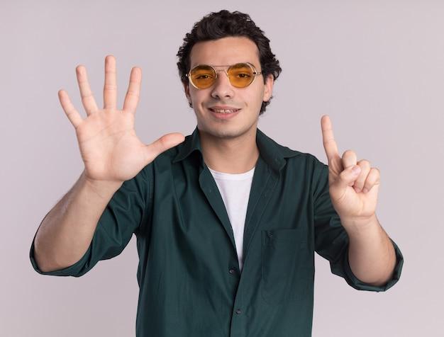 Młody człowiek w zielonej koszuli w okularach patrząc na przód uśmiechnięty pewnie pokazuje numer sześć stojący nad białą ścianą