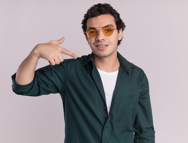 Młody człowiek w zielonej koszuli w okularach, patrząc na przód, uśmiechnięty pewnie, wskazując na siebie stojącego nad białą ścianą