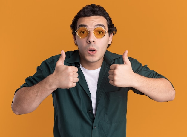 Młody człowiek w zielonej koszuli w okularach patrząc na przód zaskoczony pokazując kciuki do góry stojąc nad pomarańczową ścianą