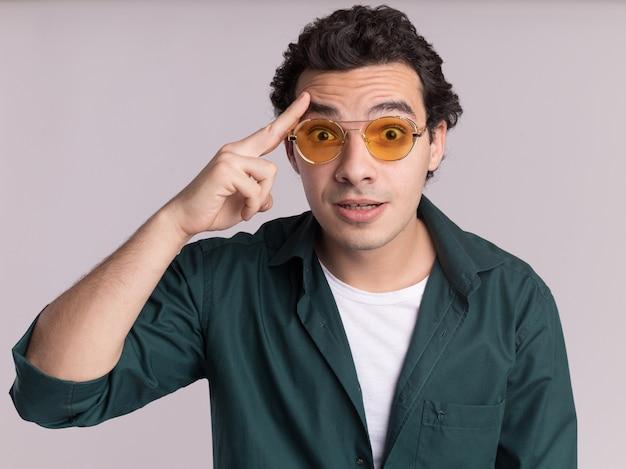 Młody człowiek w zielonej koszuli w okularach patrząc na przód zaskoczony, wskazując palcem wskazującym na swoją świątynię, mając nowy pomysł stojący nad białą ścianą