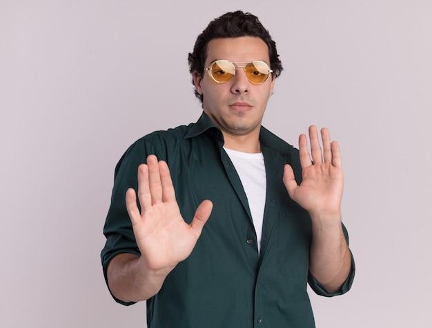 Młody człowiek w zielonej koszuli w okularach patrząc na przód zmartwiony robiąc gest obrony rękami stojącymi nad białą ścianą