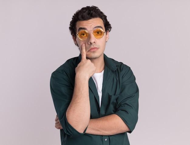 Młody człowiek w zielonej koszuli w okularach patrząc z przodu, wskazując palcem wskazującym na jego oko, czekając na coś stojącego nad białą ścianą