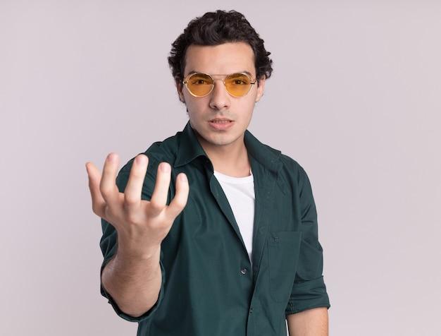 Młody człowiek w zielonej koszuli w okularach, patrząc z przodu z gniewną twarzą z podniesionym ramieniem, stojąc na białej ścianie