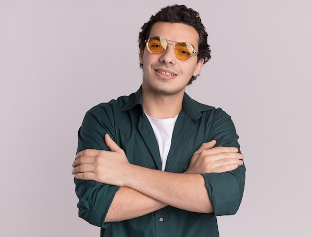 Młody człowiek w zielonej koszuli w okularach patrząc z przodu z pewnym uśmiechem na twarzy z rękami skrzyżowanymi stojąc na białej ścianie