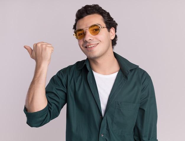 Młody człowiek w zielonej koszuli w okularach patrząc z przodu z uśmiechem na twarzy, wskazując kciukiem do tyłu stojąc na białej ścianie