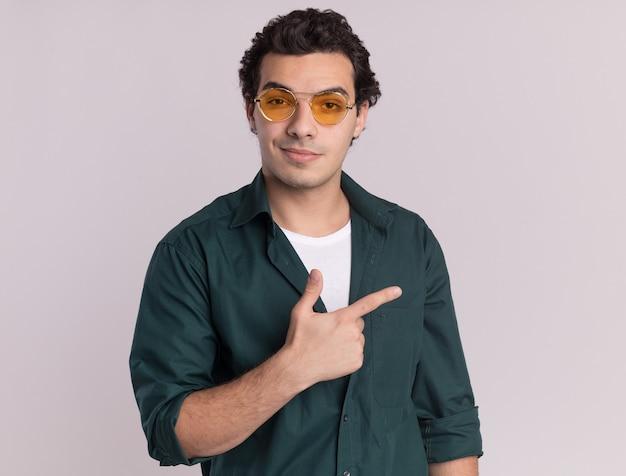 Młody człowiek w zielonej koszuli w okularach patrząc z przodu z uśmiechem na twarzy, wskazując palcem wskazującym z boku stojącego nad białą ścianą