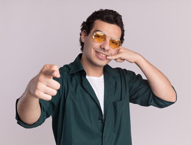 Młody człowiek w zielonej koszuli w okularach, patrząc z przodu z uśmiechem na twarzy, wskazujący palcem wskazującym na aparat, wykonujący wezwanie do mnie gest stojący nad białą ścianą