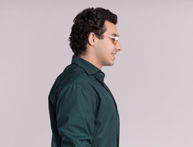 Młody człowiek w zielonej koszuli w okularach stojących bokiem z uśmiechem na twarzy na białej ścianie