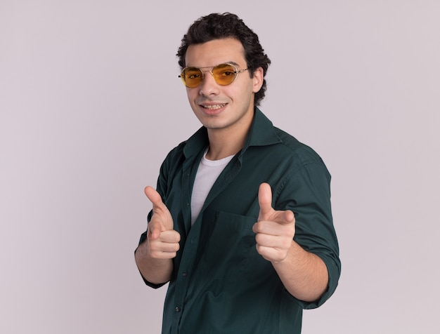 Młody człowiek w zielonej koszuli w okularach, wskazując palcami wskazującymi z przodu szczęśliwy i pozytywny stojący nad białą ścianą