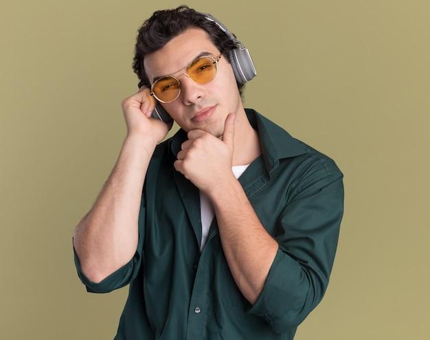 Młody człowiek w zielonej koszuli w okularach ze słuchawkami, patrząc z przodu z zamyślonym wyrazem myśli stojącej nad zieloną ścianą