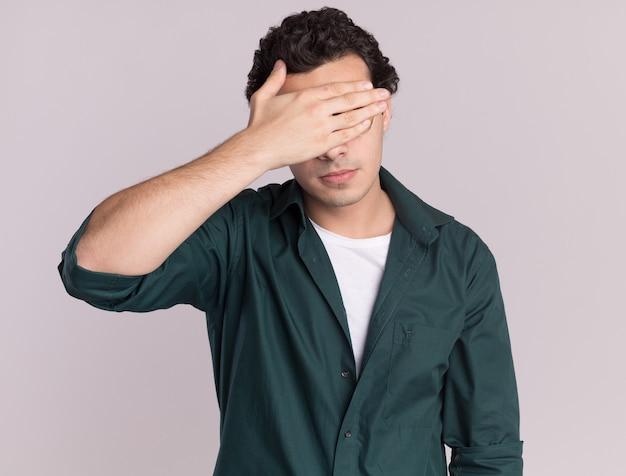 Młody człowiek w zielonej koszuli zmęczony i znudzony zamykając oczy ręką stojącą na białej ścianie