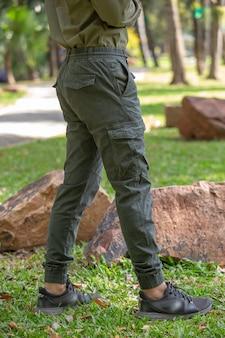Młody człowiek w zielonych spodniach stojący w parku