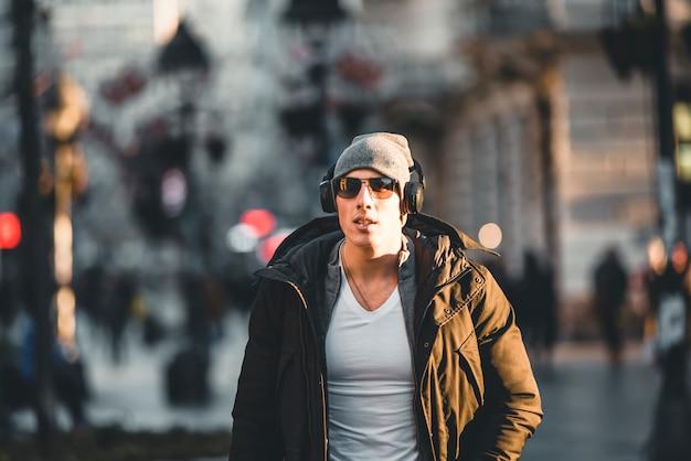 Młody człowiek w zimowych ulicach miasta ze słuchawkami