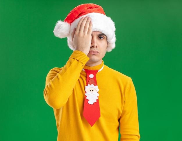 Młody człowiek w żółtym golfie i czapce mikołaja z zabawnym krawatem patrząc na kamerę z poważną twarzą zakrywającą jedno oko ręką stojącą na zielonym tle