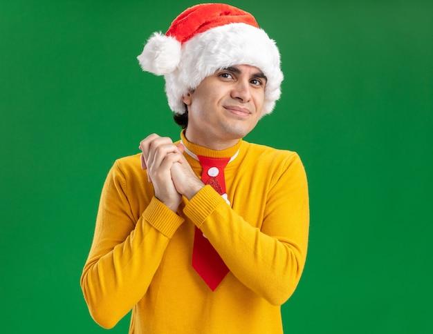 Młody człowiek w żółtym golfie i czapce mikołaja z zabawnym krawatem, trzymając się za ręce razem szczęśliwy i wesoły, czekając na niespodziankę stojącą na zielonym tle