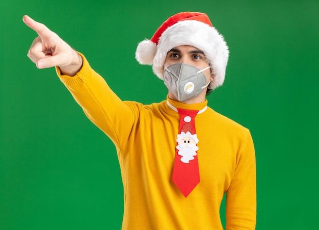 Młody człowiek w żółtym golfie i czapce mikołaja z zabawnym krawatem w masce ochronnej na twarz patrząc na bok, wskazując palcem wskazującym na coś stojącego nad zieloną ścianą