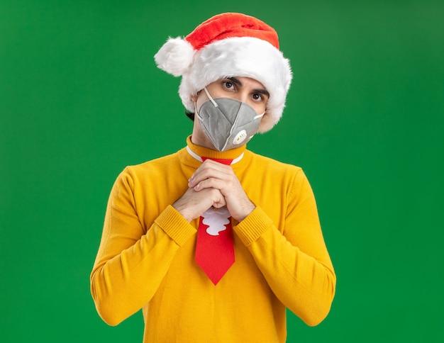 Młody człowiek w żółtym golfie i czapce mikołaja z zabawnym krawatem w masce ochronnej na twarz patrząc na kamerę, trzymając ręce razem, stojąc na zielonym tle