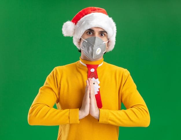 Młody człowiek w żółtym golfie i czapce mikołaja z zabawnym krawatem w masce ochronnej na twarz trzymając się za ręce razem z poważną twarzą stojącą nad zieloną ścianą