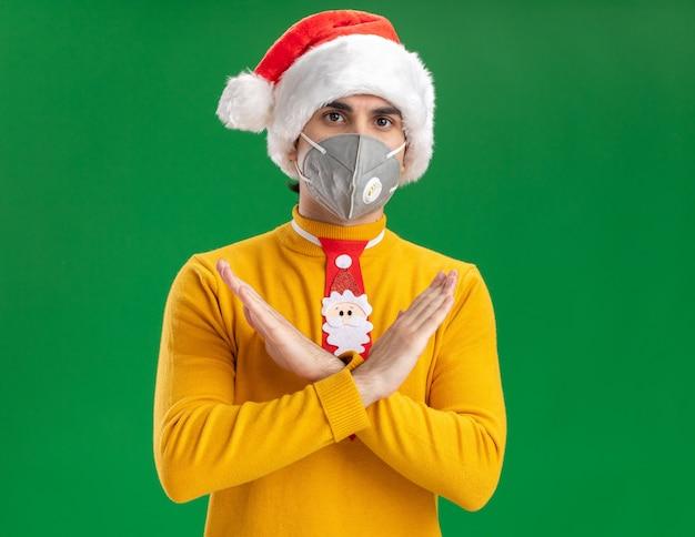 Młody człowiek w żółtym golfie i czapce mikołaja z zabawnym krawatem w masce ochronnej na twarz wykonujący gest stopu krzyżujący ręce patrząc na kamerę z poważną twarzą stojącą na zielonym tle