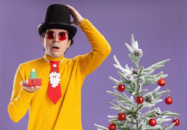 Młody człowiek w żółtym golfie i okularach na sobie czarny kapelusz i zabawny krawat trzyma kostki z numerem dwadzieścia pięć
