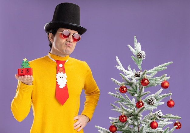 Młody człowiek w żółtym golfie i okularach na sobie czarny kapelusz i zabawny krawat trzymając kostki z numerem dwadzieścia pięć przedstawiający datę