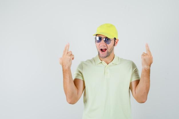 Młody człowiek w żółtym mundurze pokazuje gest pistoletu i wygląda pewnie