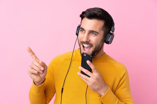 Młody człowiek w żółtym swetrze, słuchając muzyki przez słuchawki i trzymając telefon