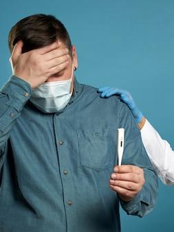 Młody człowiek w zwykłej tkaniny noszenie maski ochronne medyczne podekscytowany, zestresowany i przestraszony po przeczytaniu bardzo wysokiej temperatury wynik z termometru cyfrowego, pojęcie choroby