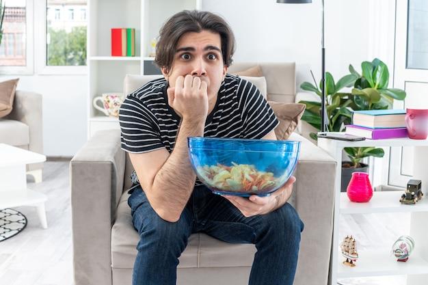 Młody człowiek w zwykłych ubraniach trzyma miskę chipsów patrząc na telewizor zestresowany i nerwowy gryzący paznokcie siedzący na krześle w jasnym salonie