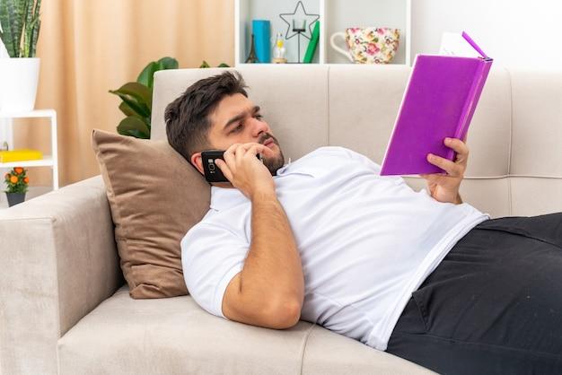 Młody człowiek w zwykłych ubraniach, trzymając książkę, czytając książkę i rozmawiając przez telefon komórkowy z poważną twarzą, spędzając weekend w domu leżąc na kanapie w jasnym salonie