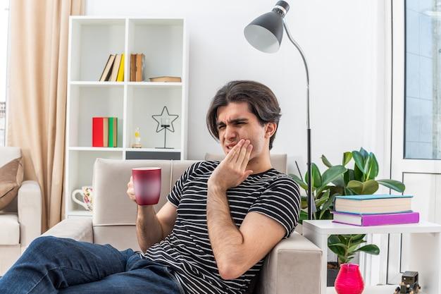 Młody człowiek w zwykłych ubraniach trzymając kubek gorącej herbaty wyglądający źle, dotykając jego policzka, czując ból zęba, siedząc na krześle w jasnym salonie