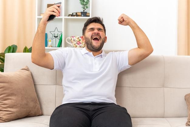 Młody człowiek w zwykłych ubraniach, trzymając smartfon szczęśliwy i podekscytowany, zaciskając pięść, ciesząc się swoim sukcesem, siedząc na kanapie w jasnym salonie