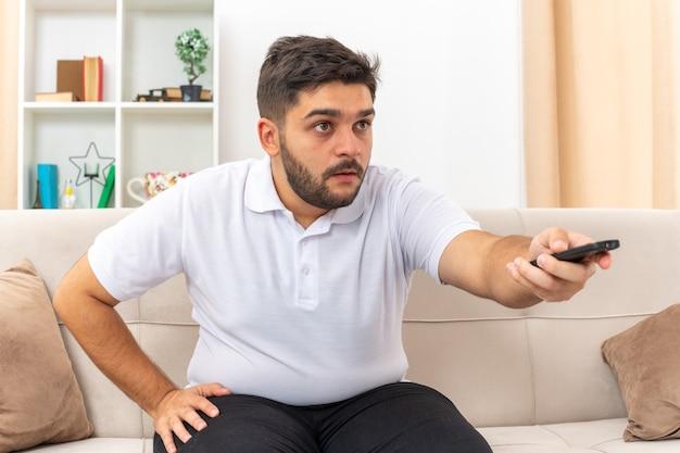 Młody człowiek w zwykłych ubraniach trzymający pilota telewizora oglądający telewizję patrząc zaintrygowany spędzający weekend w domu siedzący na kanapie w jasnym salonie