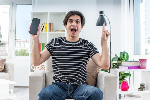 Młody człowiek w zwykłych ubraniach trzymający smartfon szczęśliwy i zaskoczony pokazujący palec wskazujący mający nowy pomysł siedzący na krześle w jasnym salonie
